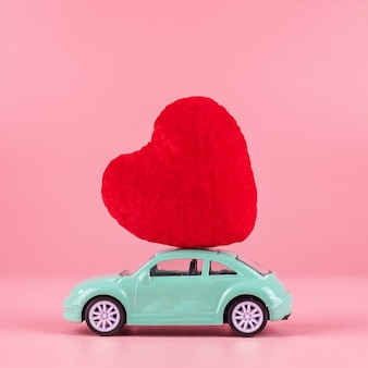 Decoração de forma de coração vermelho no brinquedo mini carro com espaço de cópia de texto em rosa. amor, casamento, romântico e feliz dia dos namorados dia conceito