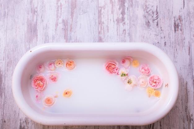 Decoração de fotografia de um antigo banho branco para bebê com rosas frescas