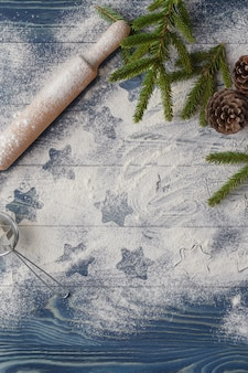 Decoração de fundo de natal. biscoitos forma estrela. farinha e temperos para um cozimento de natal em um fundo escuro.