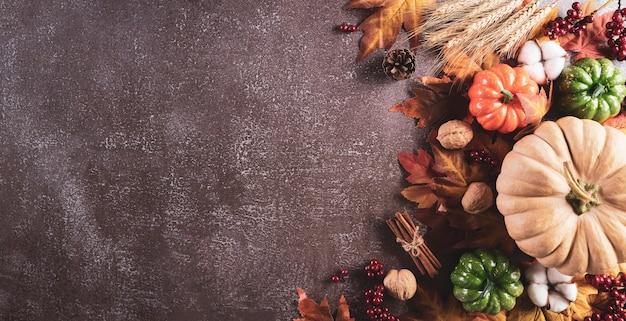 Decoração de fundo de outono e ação de graças com folhas secas, bagas vermelhas e abóbora