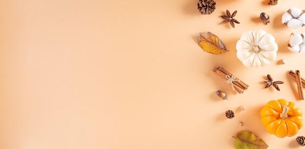 Decoração de fundo de outono e ação de graças de folhas secas, frutas vermelhas e abóbora em fundo pastel.
