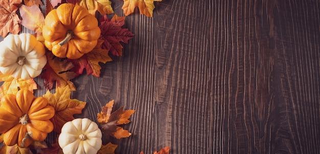 Decoração de fundo de outono e ação de graças de folhas secas, frutas vermelhas e abóbora no fundo escuro de madeira.