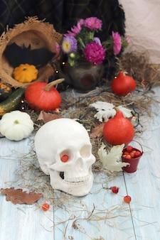 Decoração de halloween com abóboras e folhas de abóboras, iluminação de bagas em uma superfície de madeira