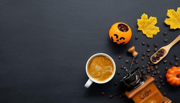 Decoração de halloween com café quente e feijão em fundo escuro. colocação plana. copie o espaço para o texto.