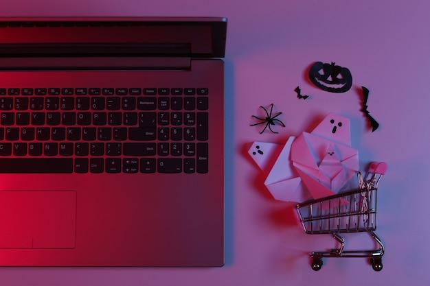 Decoração de halloween com corte de papel e laptop com carrinho de compras em luz de néon gradiente rosa azul. vista do topo. postura plana