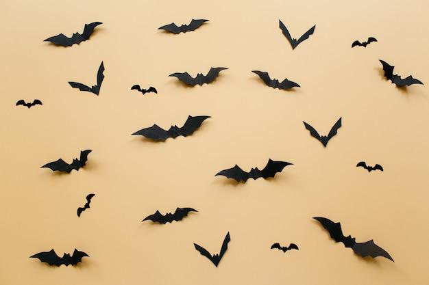 Decoração de halloween com morcegos em fundo bege pastel.
