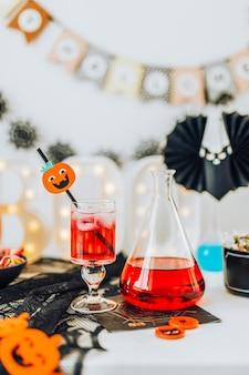 Decoração de halloween com uma bebida vermelha em um copo e um frasco