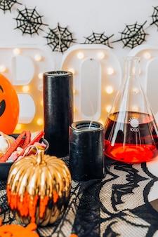 Decoração de halloween com uma jarra de abóbora e um frasco cheio de um líquido vermelho