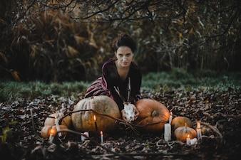 Decoração de Halloween. Mulher parece uma bruxa sentada