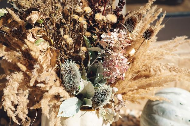 Decoração de interiores de férias de outono. grama seca natural e flores para composição rústica de ação de graças.