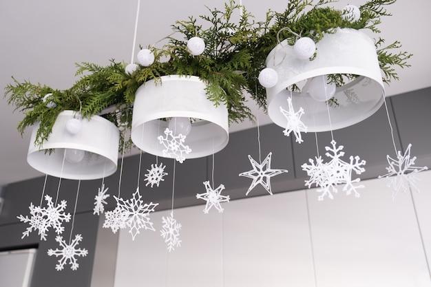 Decoração de interiores de natal branca de malha flocos de neve ramos de abeto e luzes de natal em um candeeiro.