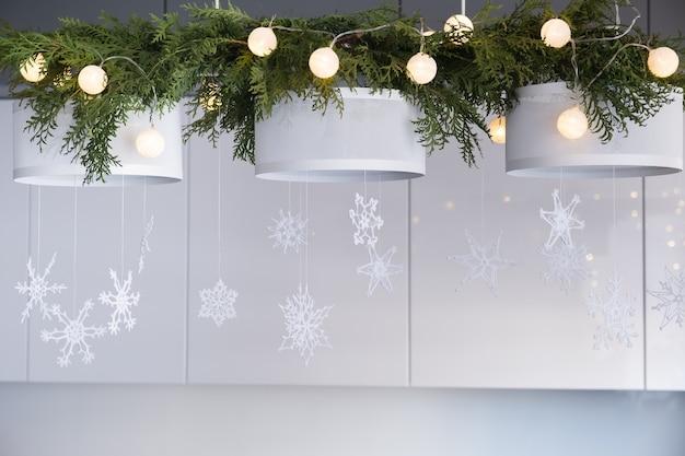 Decoração de interiores de natal tricotado flocos de neve brancos ramos de abeto e luzes de natal em um candelabro