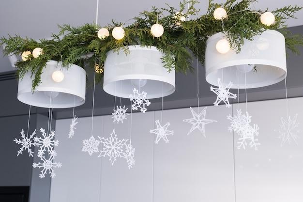 Decoração de interiores de natal tricotado flocos de neve brancos ramos de abeto e luzes de natal em um candelabro Foto Premium