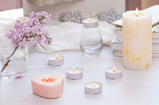 Decoração de interiores de quarto pastel com queima de velas feitas à mão, livros, flores.