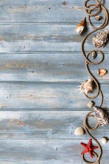 Decoração de interiores de verão com estrelas do mar, conchas, cordas e garrafas com pedras sobre fundo azul de madeira. copie o espaço. ainda vida. postura plana