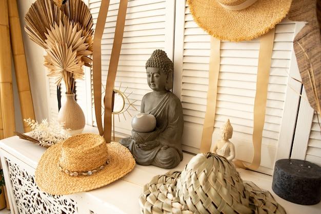 Decoração de interiores em cores claras, na prateleira há uma estátua de buda, chapéus de palha pendurados nas paredes