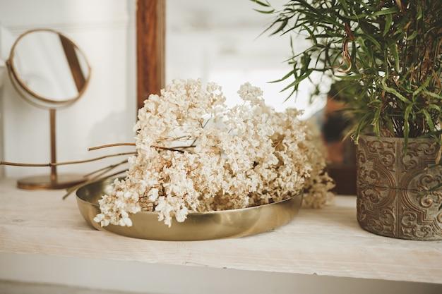 Decoração de interiores em cores claras: vaso com plantas e bandeja de flores frescas na mesa de centro