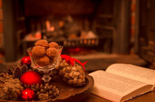 Decoração de inverno com bolas de sobremesas de chocolate em vidro alto e livro aberto em casa