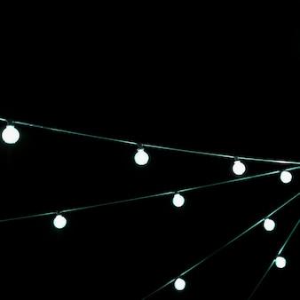 Decoração de lâmpada incandescente de natal branco contra o pano de fundo preto