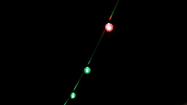 Decoração de lâmpada verde e vermelha sobre fundo preto