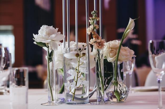 Decoração de layout de mesa de casamento romântico com grandes buquês de flores exuberantes, incluindo rosas brancas ranúnculo persa botões de ouro, orquídeas brancas e velas