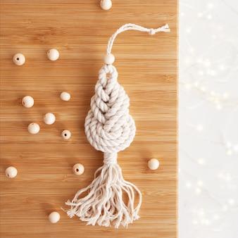 Decoração de macramé de natal. árvore de natal na placa de madeira. materiais naturais - fios de algodão, contas de madeira. eco decorações, ornamentos, decoração feita à mão. feriados de inverno e ano novo.
