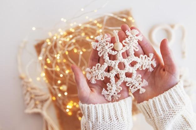 Decoração de macramé de natal. floco de neve de natal em fundo com luzes de desfoque. materiais naturais - fio de algodão. eco decorações, ornamentos, decoração feita à mão. feriados de inverno e ano novo.