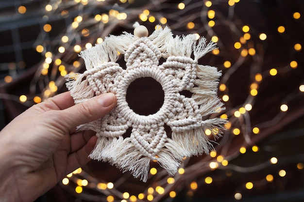 Decoração de macramé de natal. floco de neve de natal em fundo marrom escuro