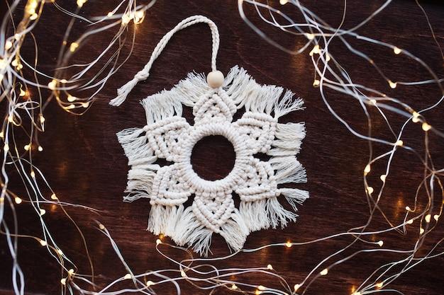 Decoração de macramé de natal. floco de neve de natal na placa de madeira de marrom escuro.