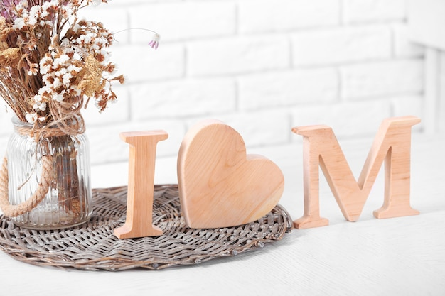 Decoração de madeira e flores para o dia das mães na parede de tijolos