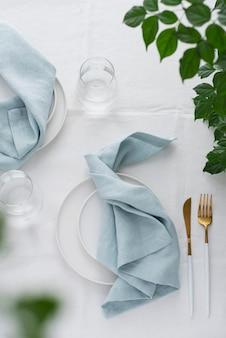 Decoração de mesa com toalha de linho branco e guardanapos azul claro, imagem de foco seletivo