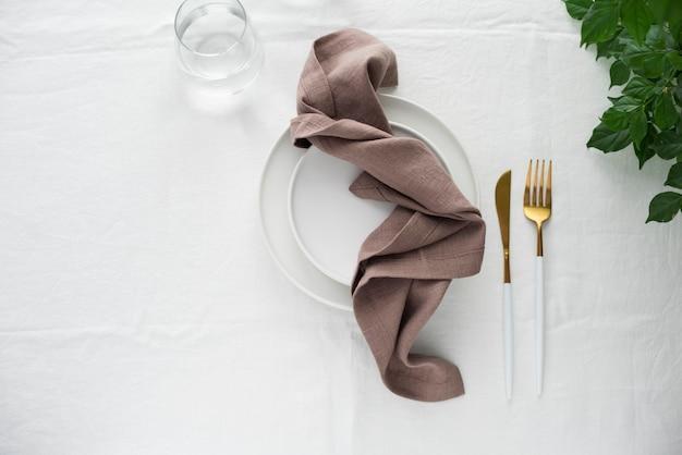 Decoração de mesa com toalha de linho branco e guardanapos marrons, imagem de foco seletivo