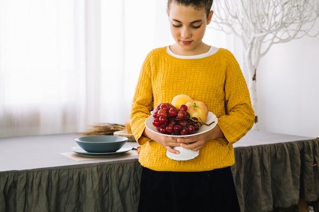 Decoração de mesa de ação de graças com mulher segurando frutas