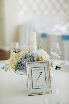 Decoração de mesa de casamento com flores azuis em cima da mesa na decoração de mesa do restaurante para o jantar no casamento.
