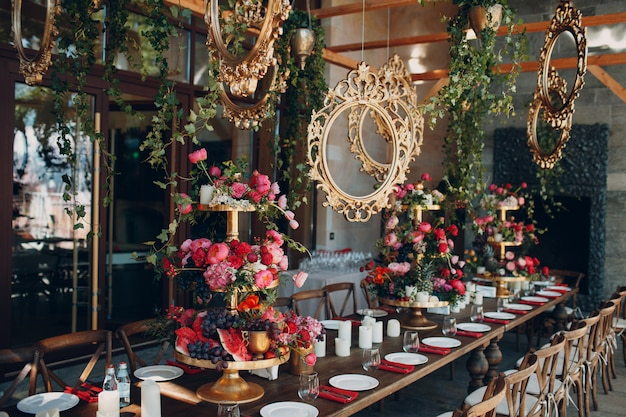 Decoração de mesa de casamento com frutas e bagas com molduras artesanais de ouro