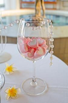 Decoração de mesa de casamento. doces de forma de coração no copo de vinho.