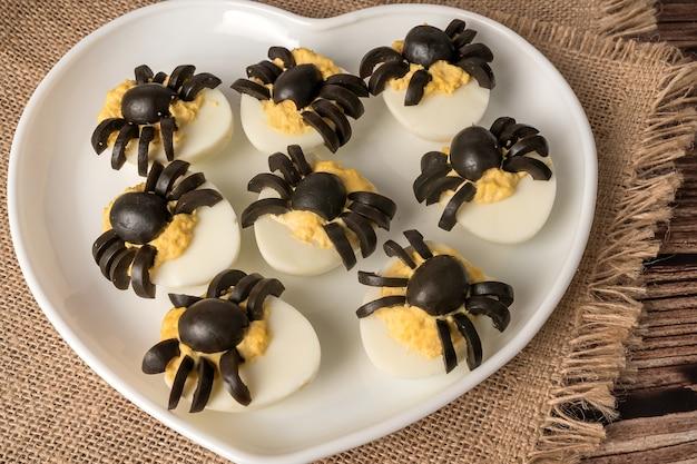 Decoração de mesa de halloween. ovo de aranhas. lanche de festa. num prato branco.