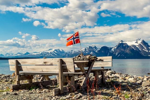 Decoração de mesa de madeira da área de parada de descanso para o local do piquenique e bandeira norueguesa na costa do fiorde do lago.