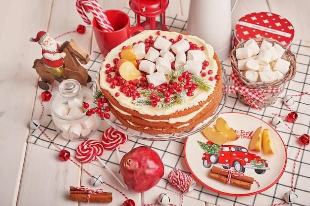 Decoração de mesa de natal, com bolo de frutas festivo e doces em cima da mesa