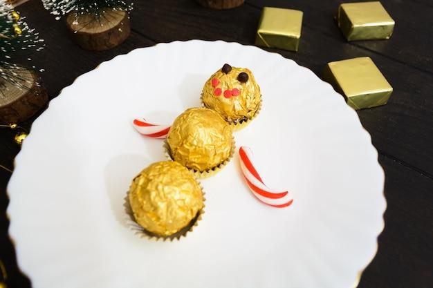 Decoração de mesa de natal com boneco de neve de doces no prato com árvore de natal