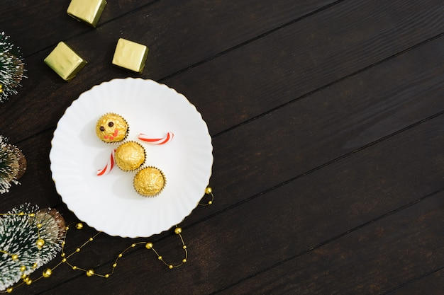 Decoração de mesa de natal com boneco de neve de doces no prato