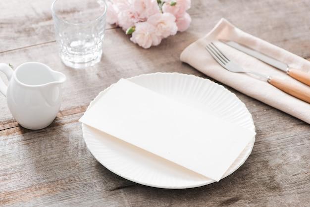 Decoração de mesa de primavera com flores. pratos brancos, garfo, faca na placa de madeira