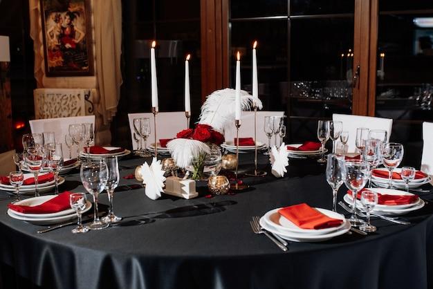 Decoração de mesas com velas acesas, decoração em tons de preto, vermelho e branco