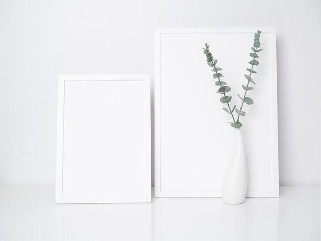 Decoração de molduras de pôster brancas com folhas de eucalipto em um moderno vaso de cerâmica branca