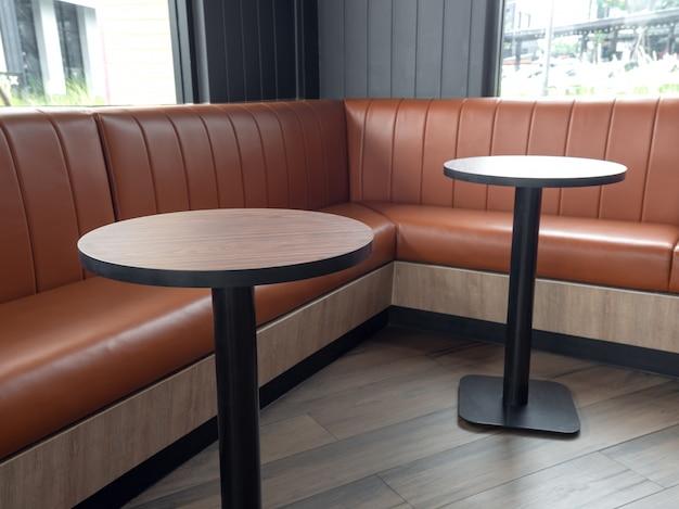 Decoração de móveis em estilo retro café. barras vazias da mesa de madeira redonda e sofá de couro longo alaranjado no assoalho de madeira.