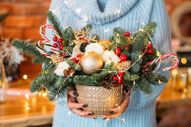 Decoração de natal artesanal. senhora segurando a panela com galhos de árvore do abeto, bastões de doces e luzes de fada.