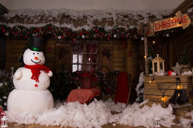 Decoração de natal atraente dentro de uma casa de madeira com grande boneco de neve de inverno, neve de algodão no chão e cabine de natal de madeira iluminada.