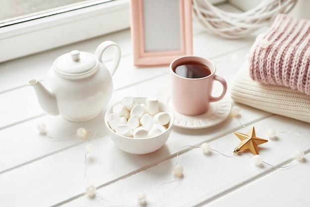 Decoração de natal, bolas, manta de lã na janela, conceito de conforto em casa, celebrações sazonais de inverno. . xícara de natal rosa com marshmallow.