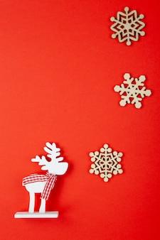 Decoração de natal, cervo de brinquedo branco com lenço xadrez, flocos de neve na parede vermelha, espaço de cópia. conceito festivo, ano novo. postura vertical plana. estilo mínimo. vista do topo.