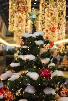 Decoração de natal colorida. férias de inverno e ornamentos tradicionais em uma árvore de natal. correntes de iluminação - lâmpadas para fundo sazonal.